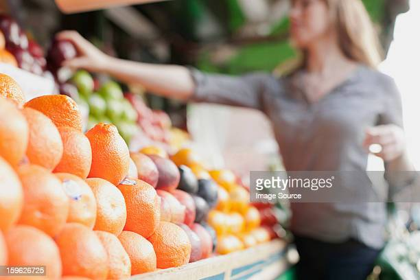 Young woman picking out fruit from stall
