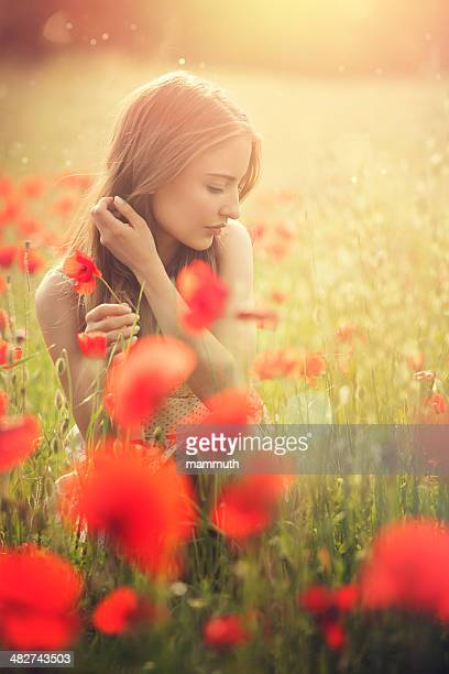 young woman picking poppies