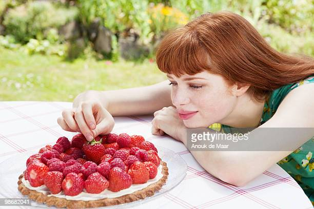 young woman picking strawberry of tart.