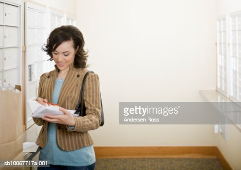 Young woman picking up mails, smiling : Stock Photo