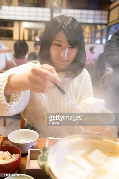 Young woman picking up tofu from hot pot