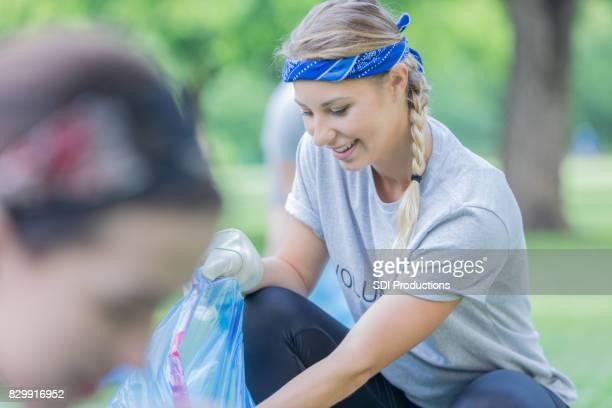 Jeune femme ramasse des ordures dans son quartier