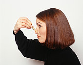 Young woman pinching nose with clothespin