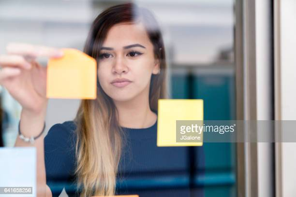 Young woman placing adhesive notes on a window