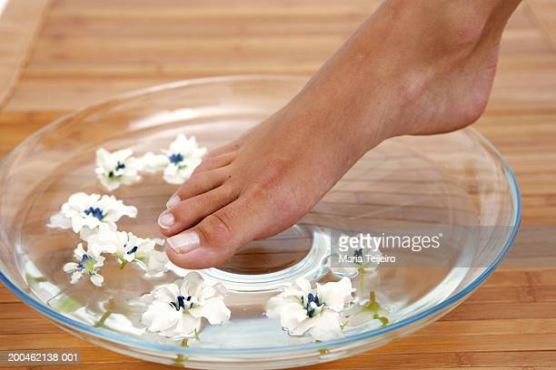 Young woman placing foot in bowl of water and petals, low section