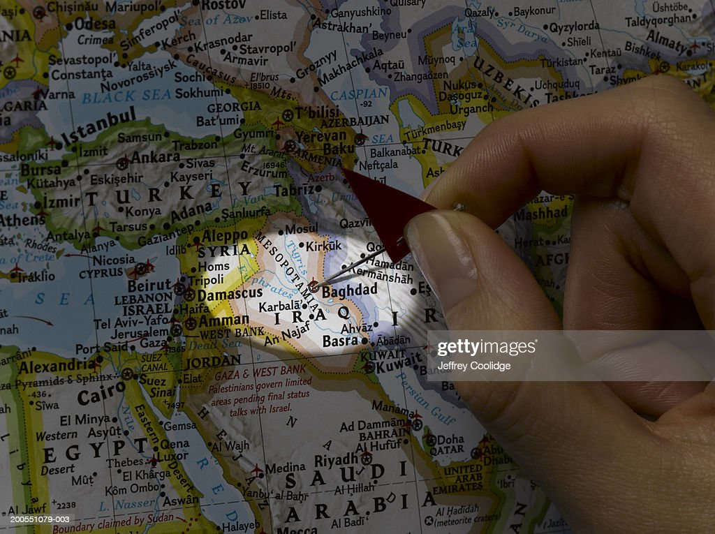 Young woman placing pin on Baghdad, Iraq on map : Stock Photo