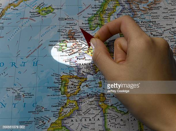 Young woman placing pin on London on map