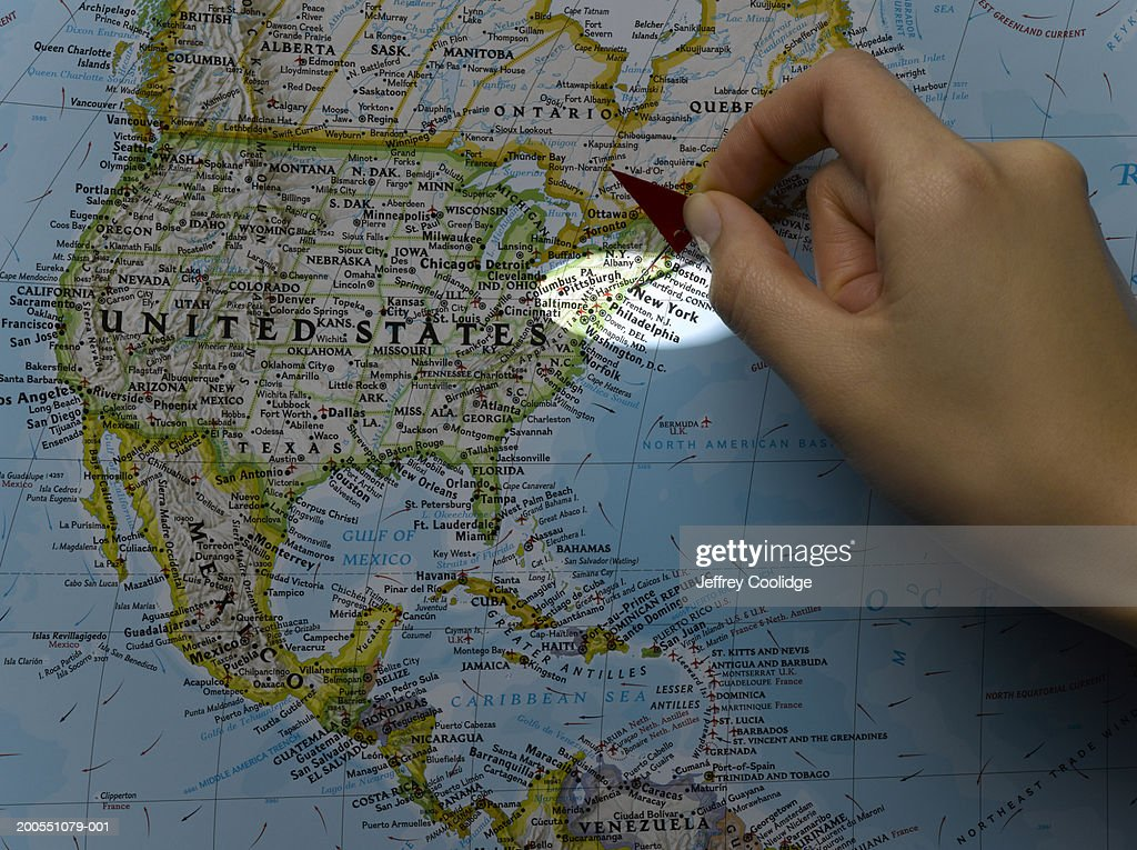 Young woman placing pin on New York City on map : Stock Photo