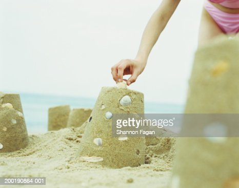 Young woman placing shell on sand castle, close-up