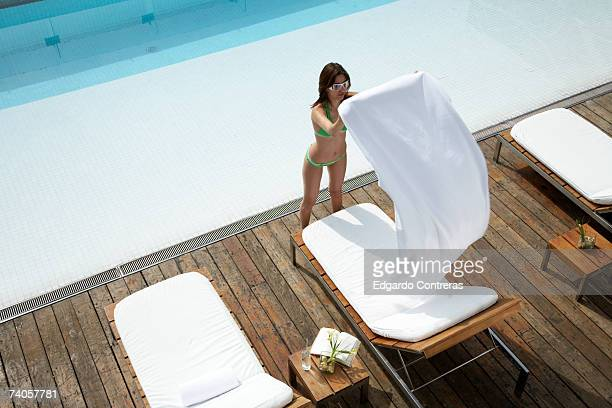 Young woman placing towel on sunlounger by swimming pool, high angle view
