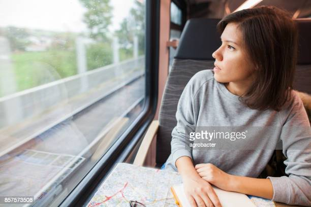 Young woman planning a trip, travelling by train