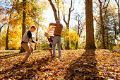 Young woman playfighting with two teenage brothers in autumn forest