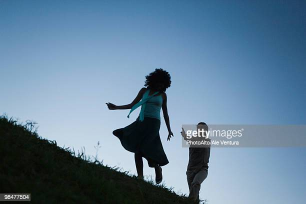 Young woman playfully running away from man in pursuit