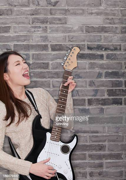 Young Woman Playing a Electric Guitar