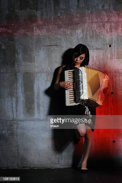 Young Woman Playing Accordian Against Cement Wall