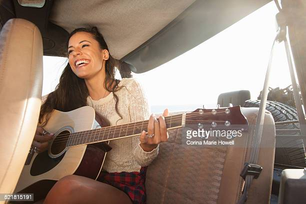 Young woman playing acoustic guitar in back of jeep