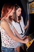 Woman playing on the machines in the amusement arcade