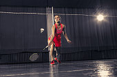 Young woman playing badminton over gym background