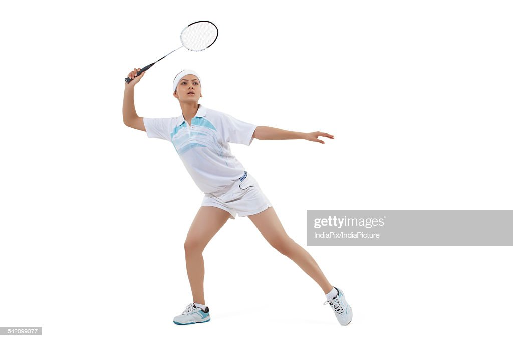 Young woman playing badminton isolated over white background
