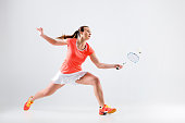 Young woman playing badminton over white studio background