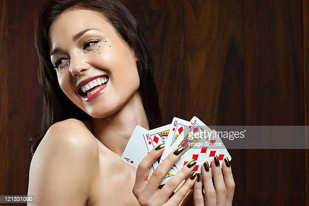 Young woman playing cards, holding royal flush