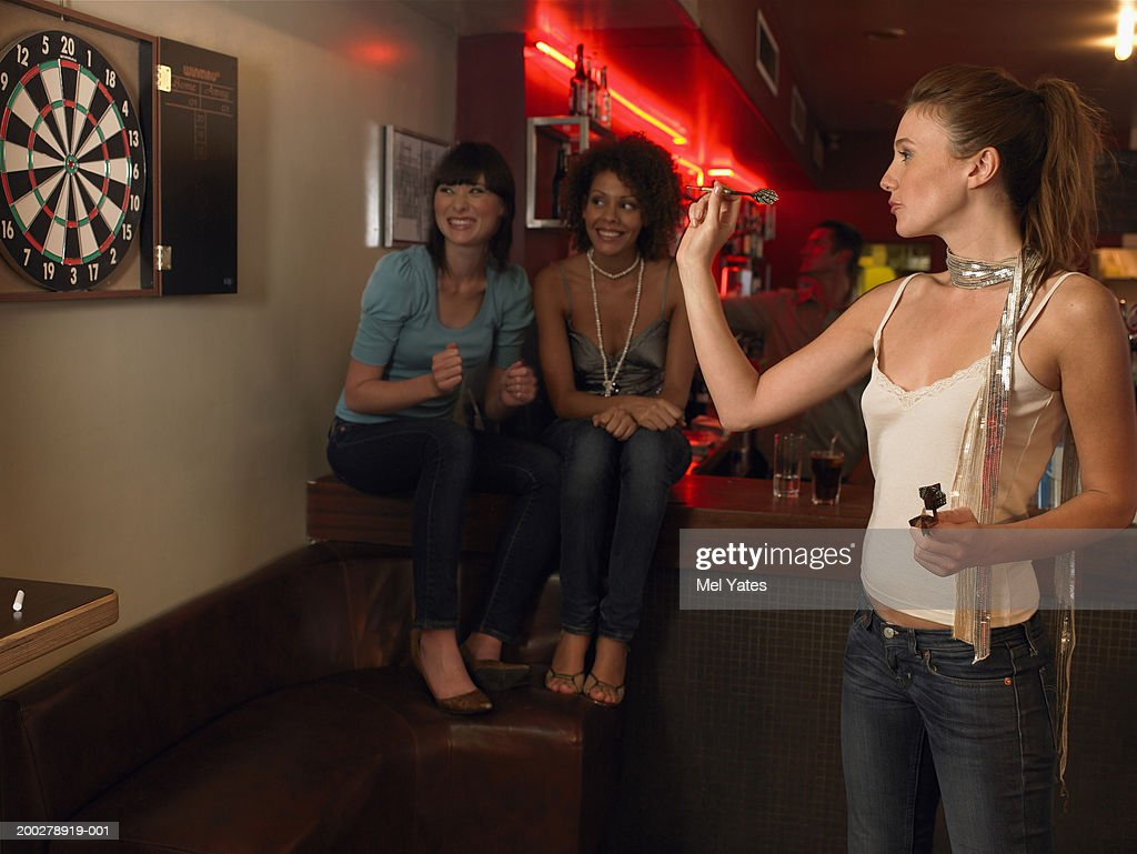 Young woman playing darts watched by two friends at bar, smiling