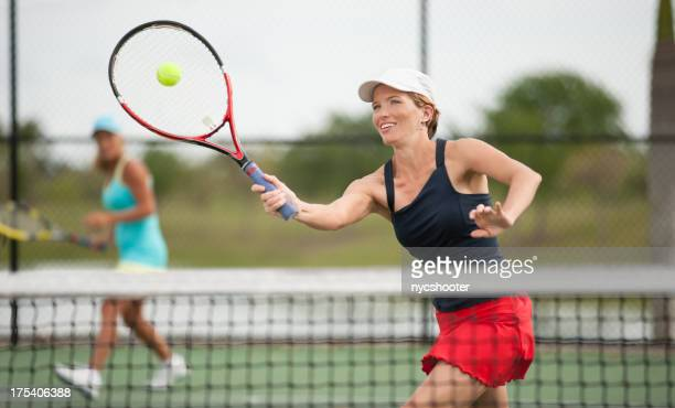 young woman playing doubles tennis