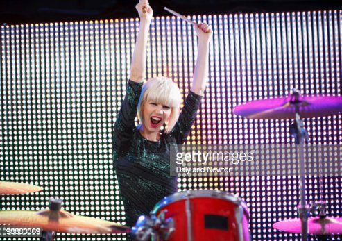 Young woman playing drums, arms raised : Stock Photo