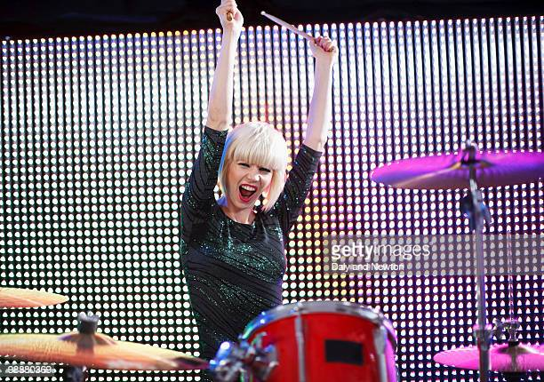 Young woman playing drums, arms raised