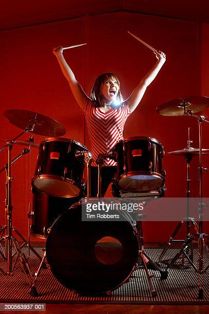 Young woman playing drums, holding drumsticks high up, yelling