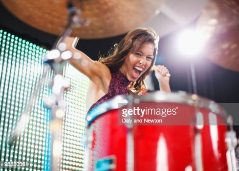 Young woman playing drums : Stock Photo