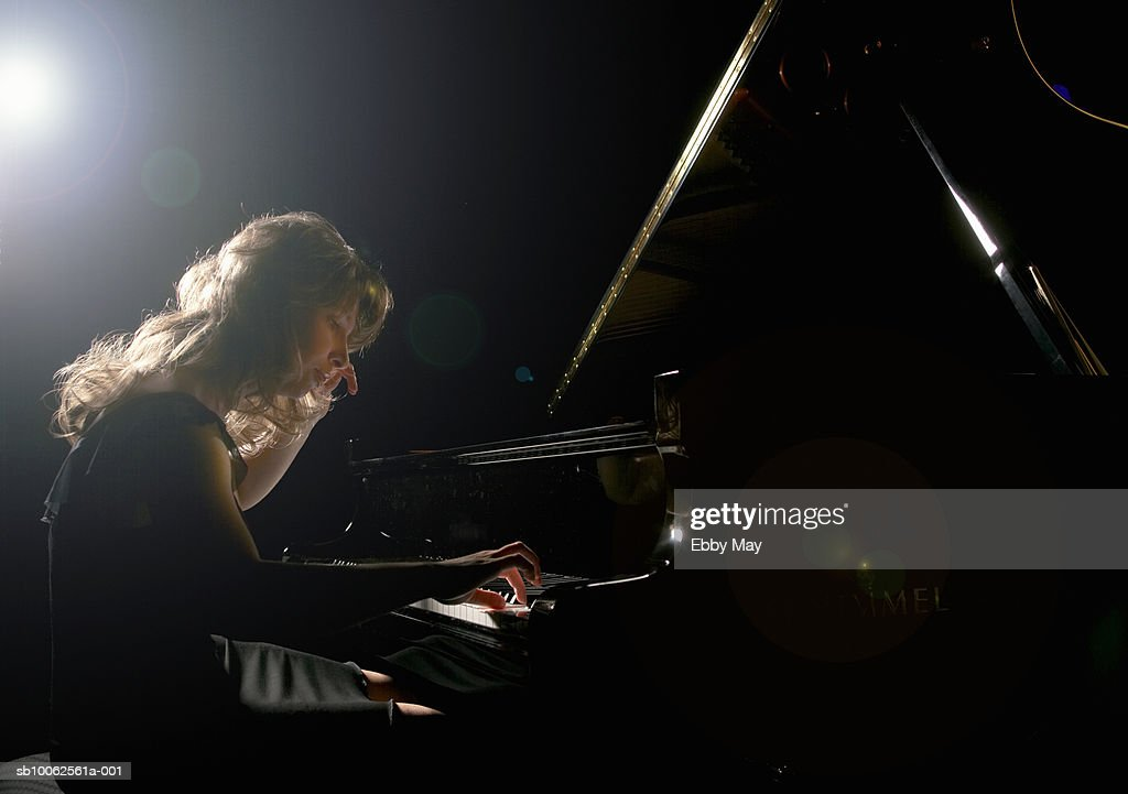Young woman playing grand piano, side view