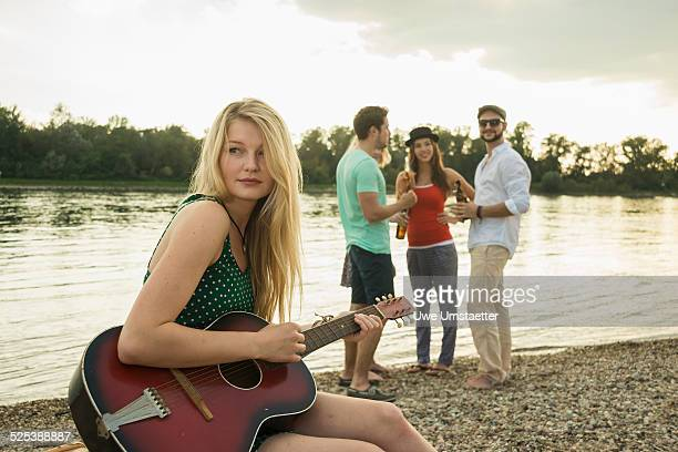 Young woman playing guitar by lake