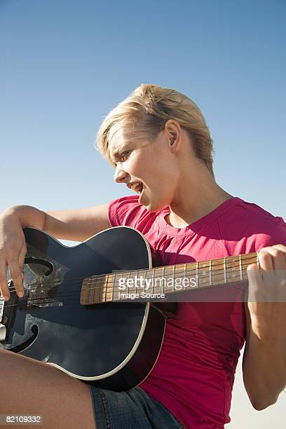 A young woman playing guitar