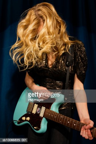Young woman playing guitar : Stock Photo