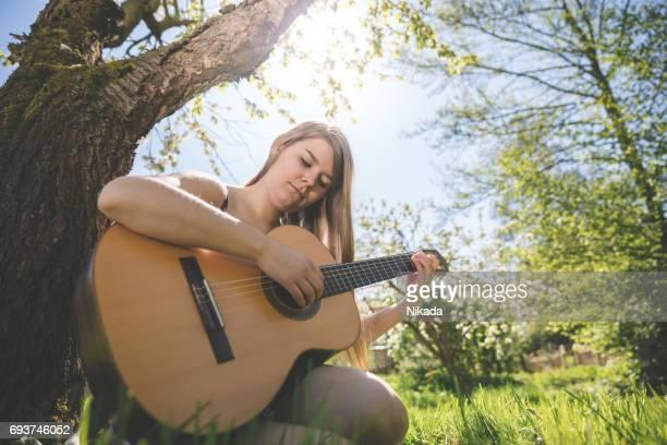 junge Frau, die Gitarre im Sitzen gegen Baum auf Wiese