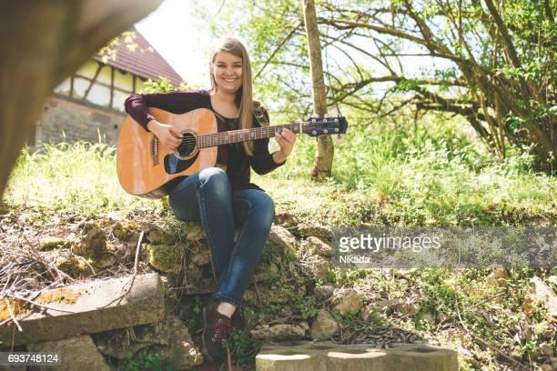 junge Frau, die Gitarre im Sitzen gegen Baum