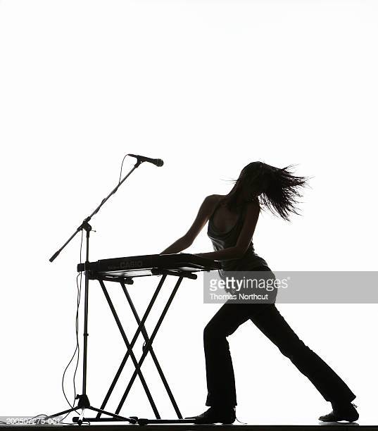 Young woman playing keyboard and tossing hair, side view