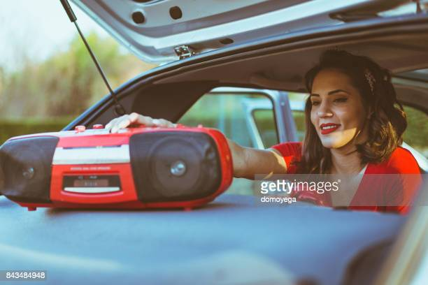 Young woman playing music on a boom box from a car