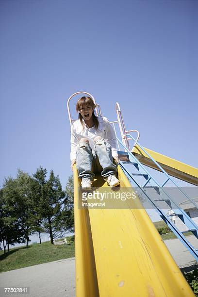 Young woman playing on a slide
