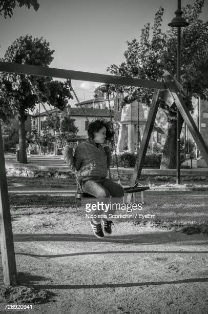Young Woman Playing On Swing At Playground
