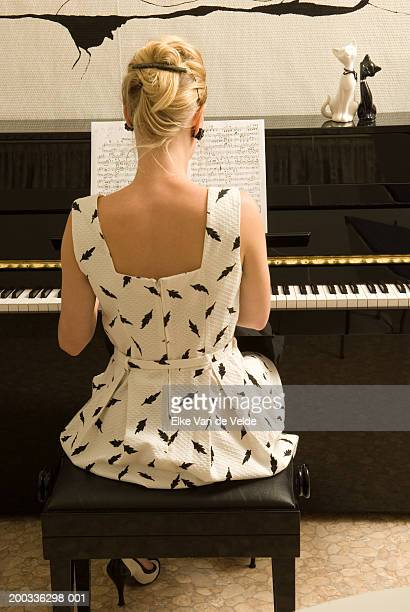 Young woman playing piano, rear view