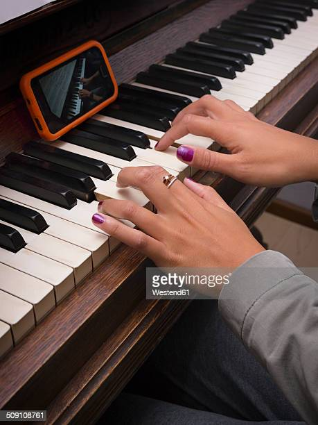Young woman playing piano with the assistance of smartphone, partial view