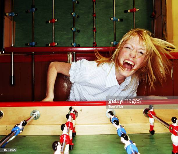 Young woman playing table football, smiling