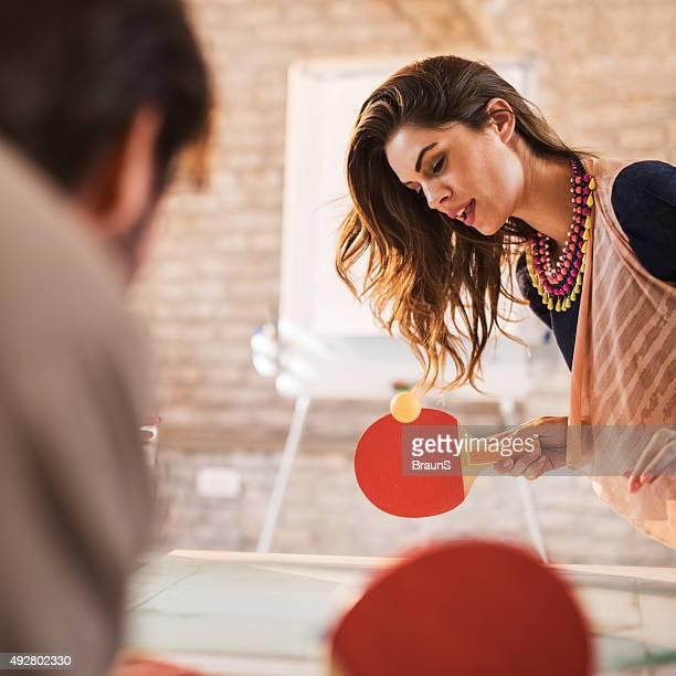 Jeune femme jouant au tennis de table avec son collègue.