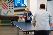 Young woman playing table tennis with her colleague