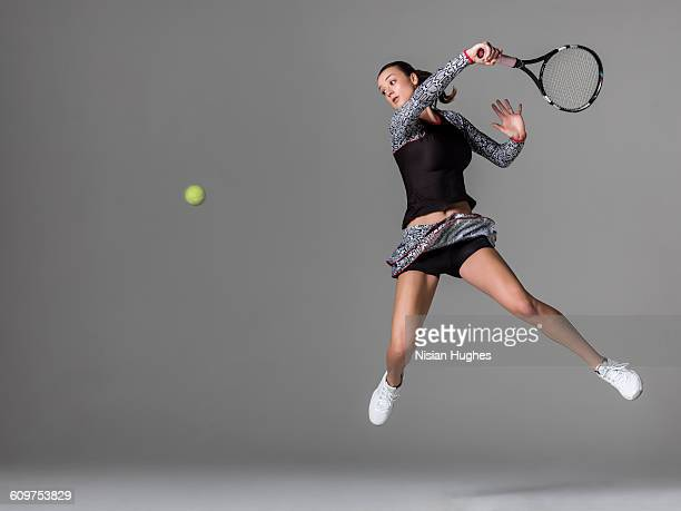 Young woman playing tennis hitting forhand