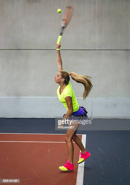 Young woman playing tennis in an indoor tennis center