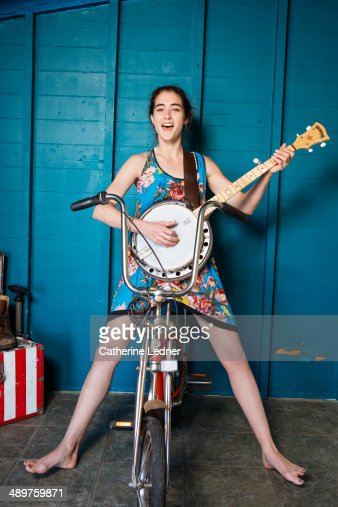 Young woman Playing the Banjo Seated on Bike