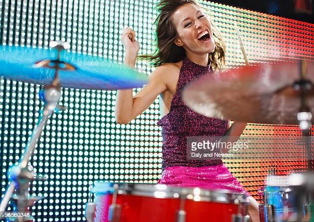 Young woman playing the drums, smiling